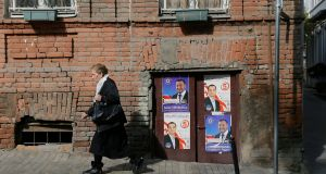 A woman passes election posters of candidates Beka Odisharia of the Georgian Dream party and Irakli Abesadze of United National Movement party, in Tbilisi, Georgia. Photograph: Zurab Kurtsikidze/EPA