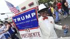 Santiago Portal, who migrated from Cuba 50 years ago, displaying a sign supporting Donald Trump in Little Havana during the Calle Ocho Festival, Miami, last March. Photograph:  Sean Drakes/Getty Images