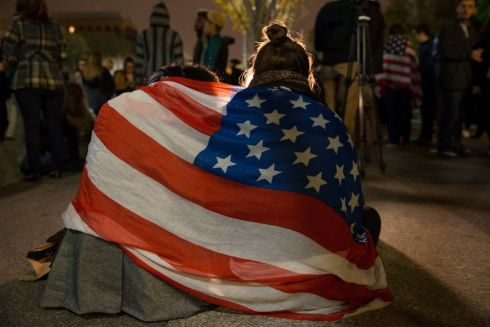 Young women cry while draped in the US national flag while sitting on Pennsylvania Avenue outside the White House just after midnight at the end of election day, in Washington, DC.   Photograph: Michael Reynolds  / EPA