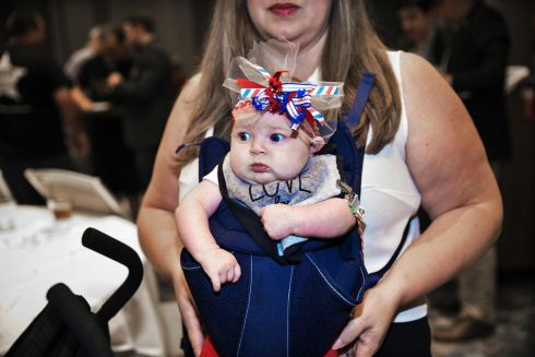 A mother carries a baby wearing a patriotic headband during a Republican election watch party in Dallas, Texas.  Photograph: Laura Buckman / AFP