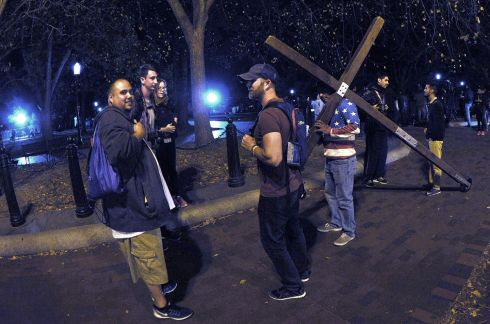 A man carries a cross as people start gathering outside the White House in Washington during the US presidential election night.  Photograph: Yuri Gripas / EPA