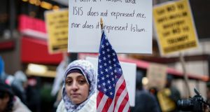 A Muslim woman holding a poster during a protest against Donald Trump's position on Muslims in New York last December. File photograph: Kena Betancur/AFP/Getty Images