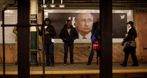 Commuters stand in front of a poster displaying an image of Russian president Vladimir Putin at the Wall Street subway station in New York. Photograph: Michael Nagle/Bloomberg