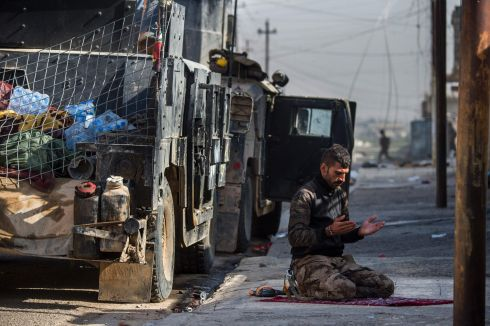 PUSHING FORWARD: An Iraqi Special Forces 2nd division soldier prays next to a Humvee military vehicle before pushing forward in the Karkukli neighbourhood of Mosul during the ongoing operation to retake the city from Islamic State.  Photograph: Odd Andersen/AFP/Getty Images