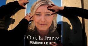 Supporters paste a poster of Marine Le Pen, France's National Front leader, on a wall in Frejus, France. Photograph: Eric Gaillard