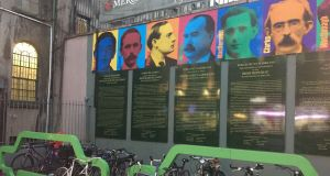 A mural in Dublin commemorating the Easter Rising and, directly underneath, two new bicycle racks in the shape of cars. Photograph: Frank McNally