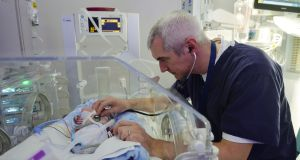 Dr Colm O'Donnell with a premature baby in the neonatal intensive care unit at the National Maternity Hospital. Photograph: Alan Betson/The Irish Times