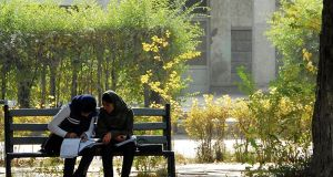 Two girls study peacefully in the grounds of Kabul University, once the scene of terrible factional fighting, on the day of the marketplace bomb depicted in this story. Photograph: Helena Mulkerns