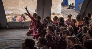Iraqi children attend school in a camp outside Mosul which it is expected will accommodate thousands of displaced people as the fighting in the Iraqi city intensifies.  Photograph: Sergey Ponomarev/New York Times