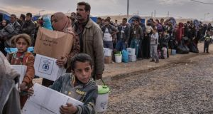 Displaced people wait in line with their possessions to be relocated to other camps at a camp near Mosul for displaced people. Photograph: Sergey Ponomarev/New York Times