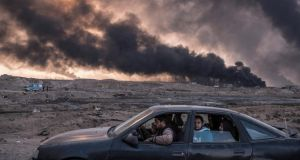 A family flees fighting as oil fields burn in Qayyara, Iraq. Photograph: Sergey Ponomarev/New York Times