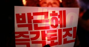 A demonstator holds candle with placard reading 'Park Geun-Hye Out' during a rally on Thursday. Photograph: EPA