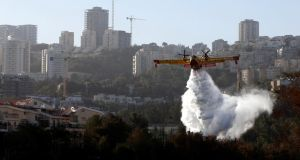 A firefighting plane drops fire-retardant over a wildfire in  the northern city of Haifa, Israel, November 25th, 2016. Photograph: Baz Ratner/Reuters
