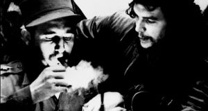 (FILES) This file photo taken in the 1960s shows then Cuban Prime Minister Fidel Castro (L) lighting a cigar while listens Argentine Ernesto Che Guevara.  Cuban revolutionary icon Fidel Castro died late on November 25, 2016 in Havana, his brother, President Raul Castro, announced on national television.  / AFP PHOTO / CUBADEBATE / Roberto SALASROBERTO SALAS/AFP/Getty Images