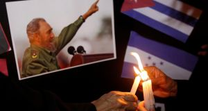 People place candles beside a picture of Fidel Castro, as part of a tribute,  in Tegucigalpa, Honduras, following the announcement of the Cuban leader's death. Photograph: Jorge Cabrera/Reuters