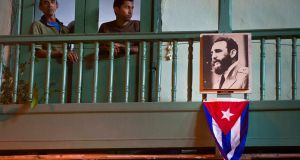 Residents stand  next to an image of the late Cuban leader Fidel Castro and a Cuban Flag in Havana, Cuba over the weekend. Photograph: Ramon Espinosa/AP Photo