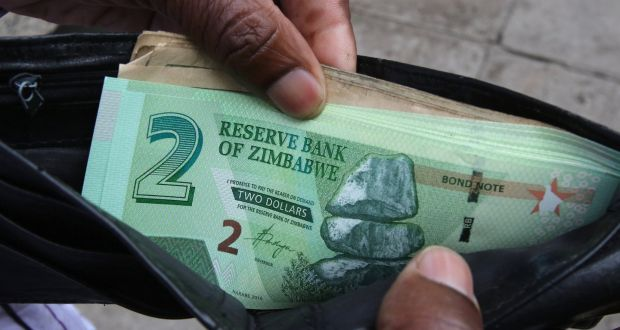 A Zimbabwean man shows off a new bond note outside a bank in Harare, Zimbabwe. Photograph: Philimon Bulawayo/Reuters