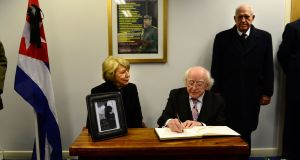 President Michael D Higgins, signs the book of condolence for former Cuban Leader Fidel Castro, at the Cuban Embassy in Dublin with his wife Sabina and Cuban Ambassador Dr. Hermes Herrera. Photograph: Dara Mac Dónaill / The Irish Times