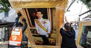 Workers lift a portrait of Thai Crown Prince Vajiralongkorn at a shop in Bangkok on Tuesday. Photograph: Dario Pignatelli/Getty Images