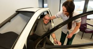 Thomas Payne, from Crumlin, practising getting into a car with senior occupational therapist  Elaine Harrington, at  Mercer's Institute for Successful Ageing  at St James's Hospital, Dublin. Photograph: Dara Mac Dónaill