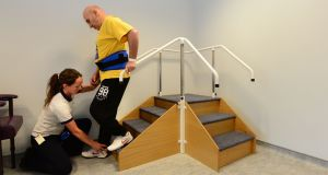 Physiotherapist Rosie Clarke with patient Gabor Karlik practising climbing stairs at the Mercer's Institute for Successful Ageing at St James's Hospital, Dublin. Photograph: Dara Mac Dónaill