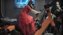 Out of this world: A  woman rides a bicycle simulator at Leke Virtual Reality  Park, a leading Chinese chain, in Beijing.