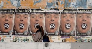 "A woman walks past posters from the far-right political movement Casapound calling for a ""No"" vote in the constitutional referendum in Rome. Photograph: Filippo Monteforte/Getty Images"