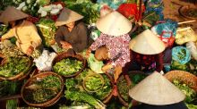 Women sell fresh produce at a street market in Hoi An