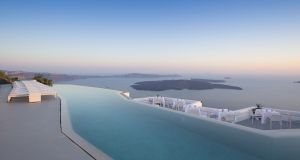 The infinity pool at Grace Santorini blends in with the Aegean Sea, behond