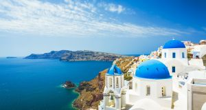 Blue-roofed churches in Oia, Santorini, look down on the caldera below