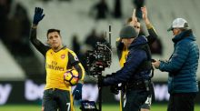 Arsenal's Alexis Sanchez celebrates with the match ball after the game. Photograph: John Sibley/Reuters