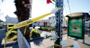 Flowers hanging from a sign post near  the scene of a warehouse fire  in the Fruitvale district of Oakland, California. Photograph: John G Mabanglo/EPA.