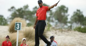 Tiger Woods reacts after holing a putt on the third hole during the final round at the Hero World Challenge golf tournament in Nassau, Bahamas. Photo: Lynne Sladky