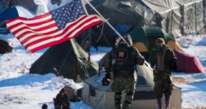 US navy veteran Rob McHaney holds an American flag as he leads a group of activists back from a police barricade on a bridge near Oceti Sakowin camp. Photograph: Jim Watson/AFP/Getty Images