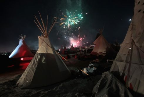A determined Native American campaign has prevented an oil pipeline passing under a damned section of the Missouri River in North Dakota. Fireworks fill the night sky above Oceti Sakowin Camp as activists celebrate the decision to deny access to the pipeline.  Photo by Scott Olson/Getty Images
