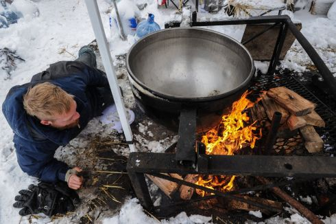 A man makes a fire under a large cooking pot in the Oceti Sakowin camp during a protest against plans to pass the Dakota Access pipeline near the Standing Rock Indian Reservation, near Cannon Ball, North Dakota, U.S. November 29th.  Photograph: Stephanie Keith  /Reuters