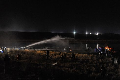 Police use a water cannon to put out a fire started by protesters during a protest against plans to pass the Dakota Access pipeline near the Standing Rock Indian Reservation, near Cannon Ball, North Dakota, U.S. November 20th.  Photograph: Stephanie Keith / Reuters