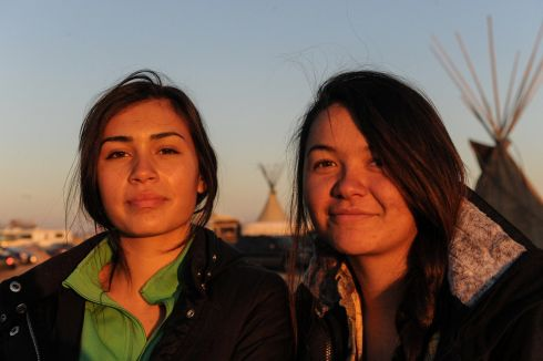 Waskoness Pitawanakwat, 16, (L) from the Ojibwe tribe and Tea McGinnis ,18, (R) from the Hupa tribe pose for a photograph in an encampment during a protest against plans to pass the Dakota Access pipeline near the Standing Rock Indian Reservation, near Cannon Ball, North Dakota, U.S. November 20th.   Photograph: Stephanie Keith / Reuters