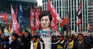 Members of the Korean Confederation of Trade carry an effigy of president Park Geun-Hye Park Geun-hye as they march during a protest against her. Photograph: Jeon Heon-Kyun/EPA