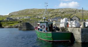 Last stop: a fishing trawler  moored in a harbour on Inishturk.  Photograph: Pete Ryan/National Geographic/Getty