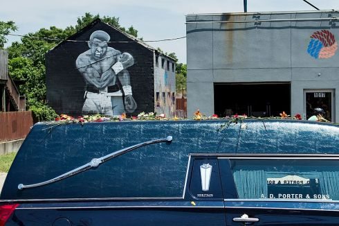 A hearse with the remains of boxing legend Muhammad Ali passes a mural depicting his 1965 victory over Sonny Liston on the way to Cave Hill Cemetery in Louisville, Kentucky. Photo: Brendan Smialowski/Getty Images
