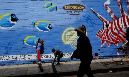 SOUTH AFRICA: A man walks past a new piece of graffiti art painted on a wall in downtown Johannesburg, South Africa. The art work, which depicts an underwater world with fish and a turtle, is in the Maboneng area of the biggest city in the country. Photograph: Kim Ludbrook/EPA
