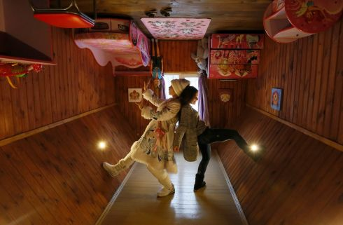 SNOW MAIDEN: A visitor and an employee dressed as Snegurochka (Snow Maiden), the granddaughter of Ded Moroz (Russian equivalent of Santa Claus), pose for a picture inside an upside down house, constructed as an attraction for tourists at the Royev Ruchey Park of Flora and Fauna in the suburbs of Krasnoyarsk, Russia. Photograph: Ilya Naymushin/Reuters