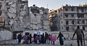 Syrian residents flee violence in the eastern rebel-held parts of Aleppo through the Bab al-Hadid district after it was seized by government forces. Photograph: George Ourfalian/AFP/Getty