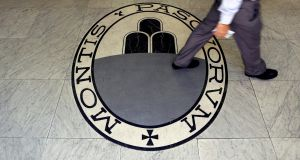 A man walks on the logo of the Monte dei Paschi di Siena bank in Rome. Photograph:  Alessandro Bianchi/Reuters