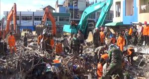 Rescuers use excavators to search for victims in the rubble of collapsed buildings. Photograph: AP