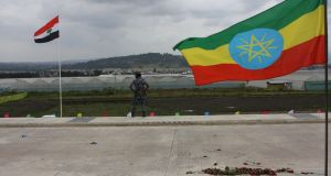 A federal policeman stands guard between the Oromo regional flag (left) and Ethiopia's national flag at the ceremony marking the opening of the Addis Ababa-Djibouti railway. Photograph: James Jeffrey