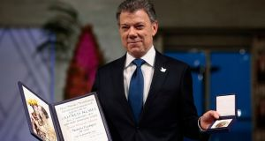Colombian president Juan Manuel Santos poses with the medal and diploma at the  ceremony in Oslo on Saturday. Photograph: Haakon Mosvold Larsen/AP