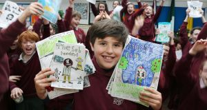 Fourth class pupil Rory Gavin (10) displays some of the story books handwritten and illustrated by classmates at Scoil Iognáid in Galway. Photograph: Joe O'Shaughnessy