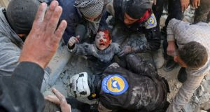 Syrian civil defence volunteers, known as the White Helmets, rescue a boy from the rubble following a reported barrel bomb attack on the Bab al-Nairab neighbourhood of Aleppo on November 24th. Photograph: Ameer Alhalbi/AFP/Getty Images